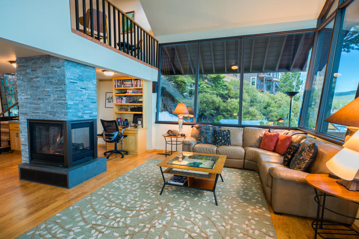 A leather sectional wraps around the first floor living area, where a 3-sided fireplace stands in the center.