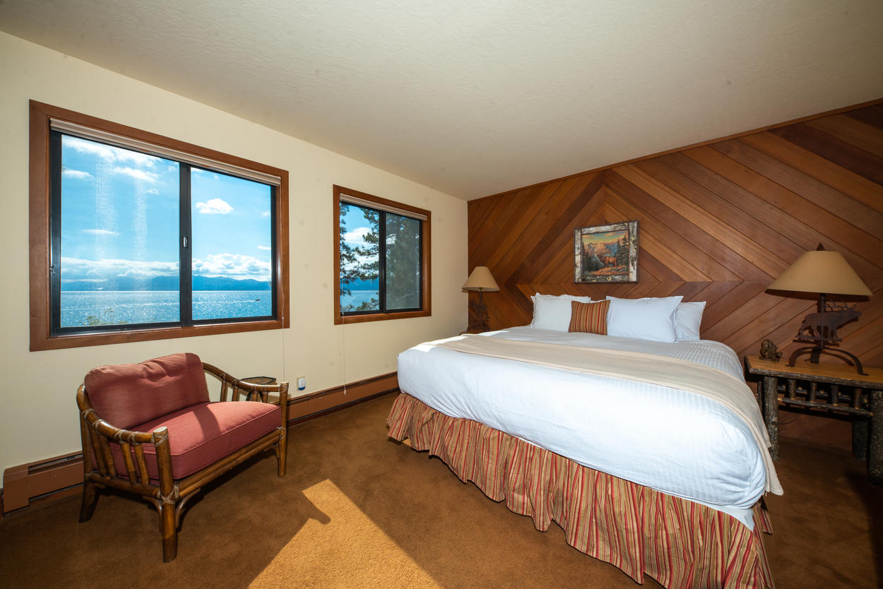 Guest bedroom 3, on the middle level of the home, has lake views and a wood-adorned wall