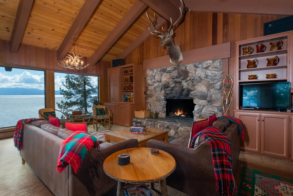 Soft leather couches adorn the expansive lakefront view to make this living room a picturesque gathering spot