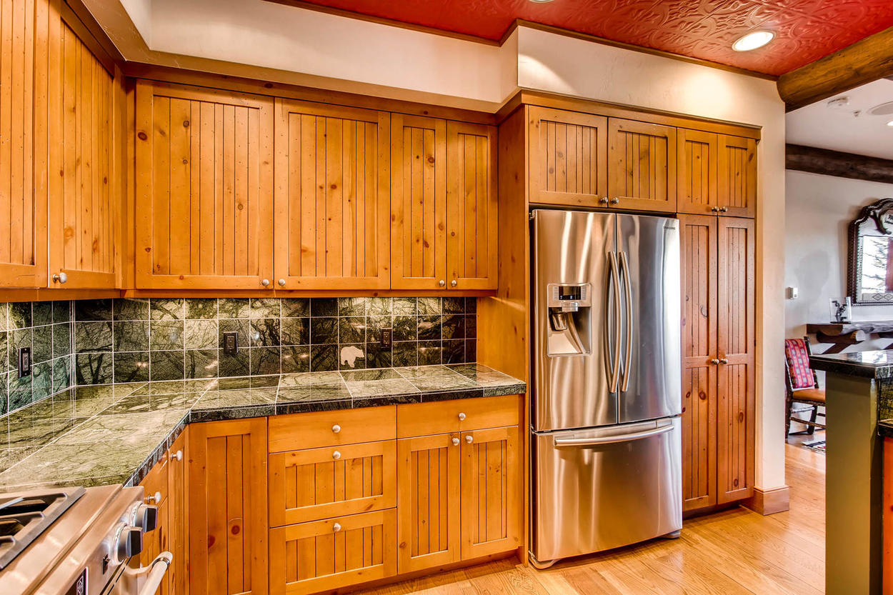 Modern lighting meets traditional natural wood decor in this sleek kitchen.