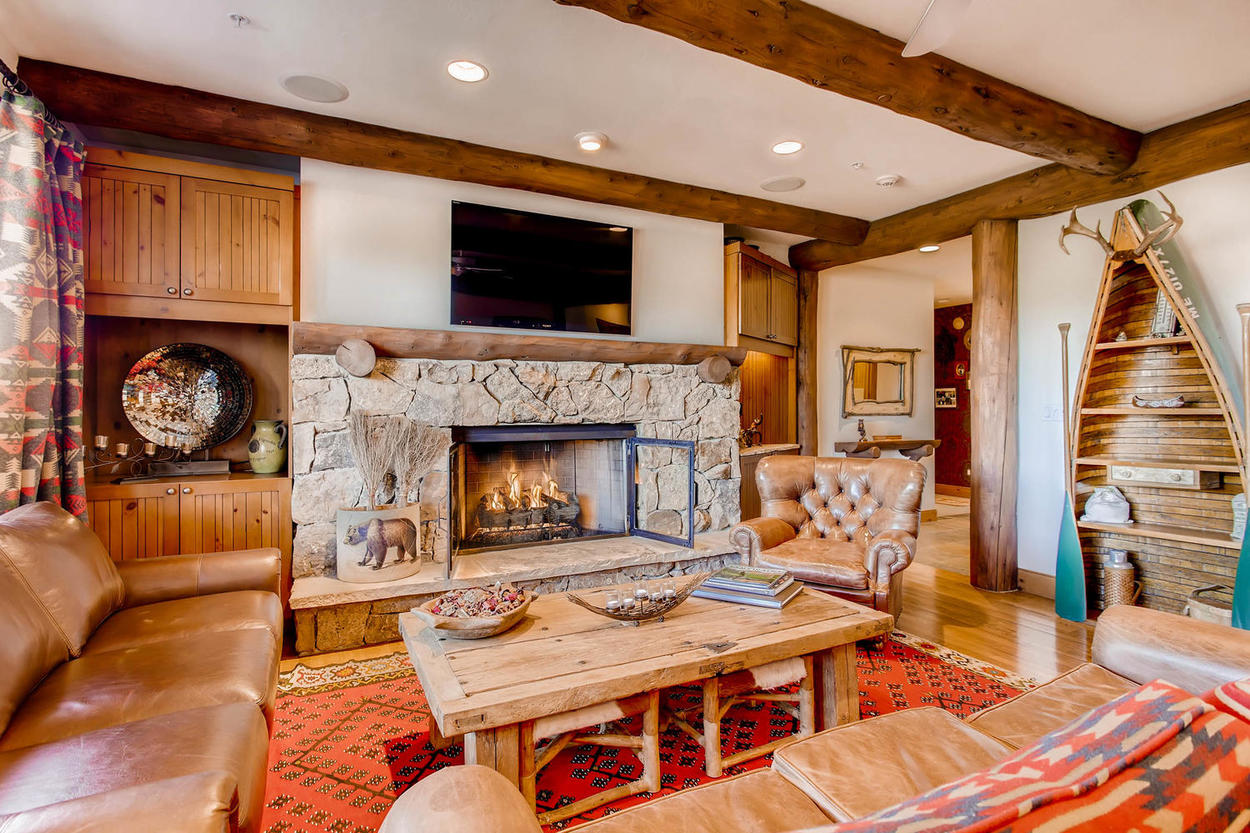The canoe shelving, crafted wood, and leather furniture create a traditional lodge atmosphere in the living area.