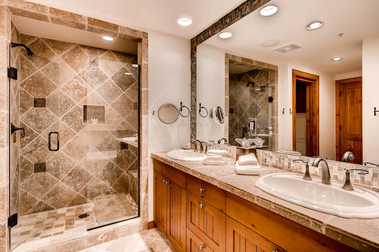The elegant master bathroom includes a large stand-alone shower and wall-size double vanity.