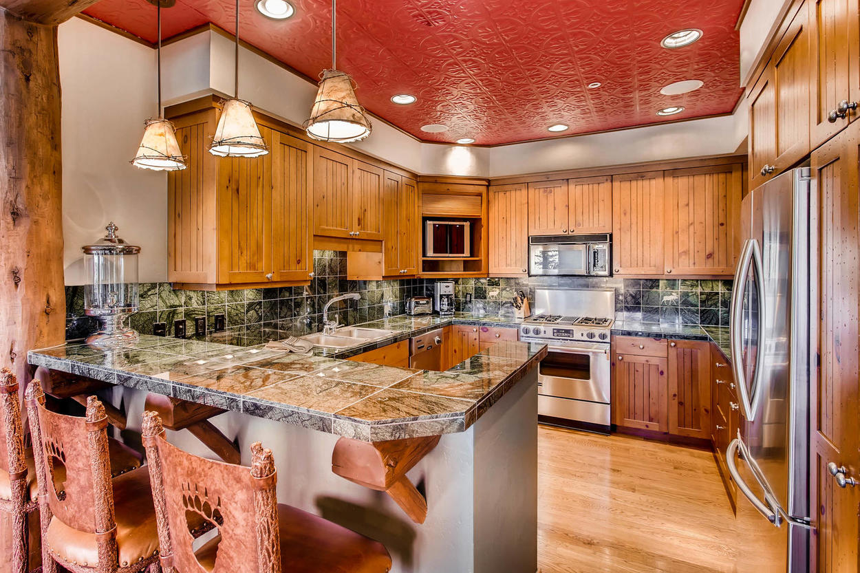 The stainless steel appliances in the kitchen pair well with its natural wood and forest green tile design.