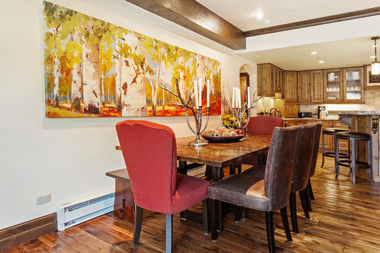 The grand dining table has seating for eight guests, and features artful mountain decor.