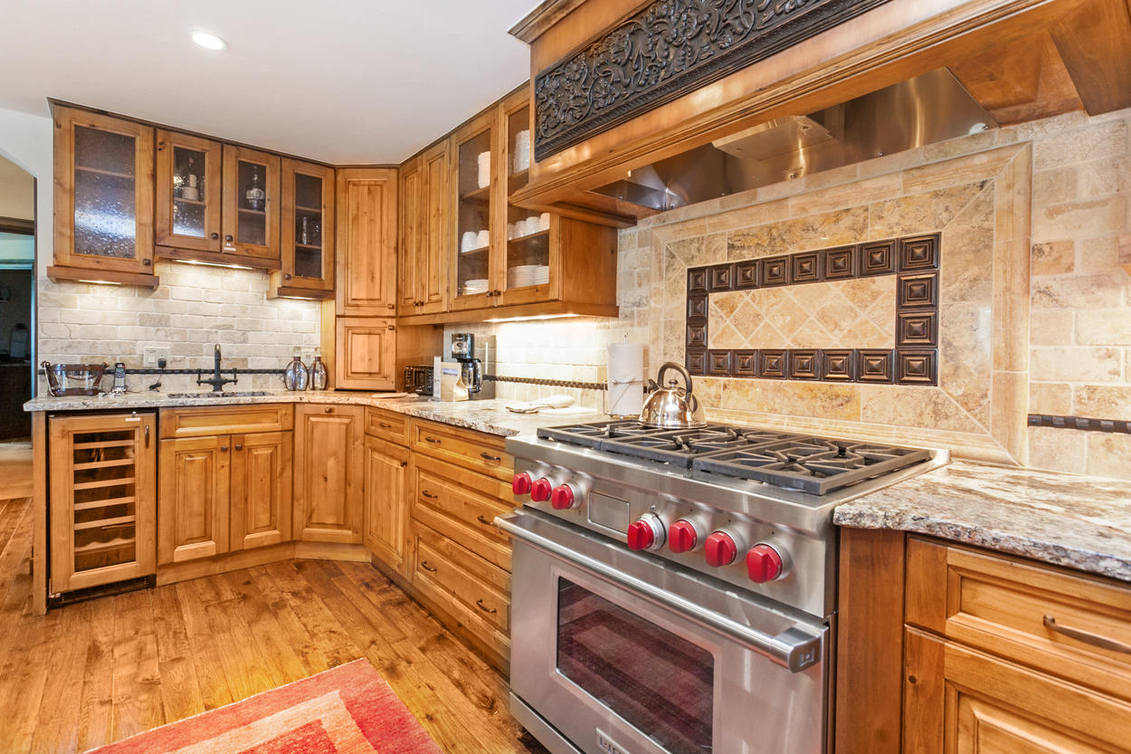 A stainless steel six-burner Wolf gas stove and wine fridge add to the luxury of this fine kitchen.