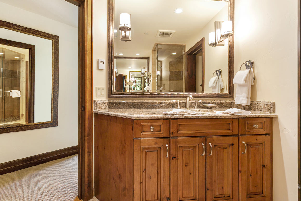 This bedroom's attached ensuite bathroom has a two vanities, walk-in shower, and separate soaking tub.