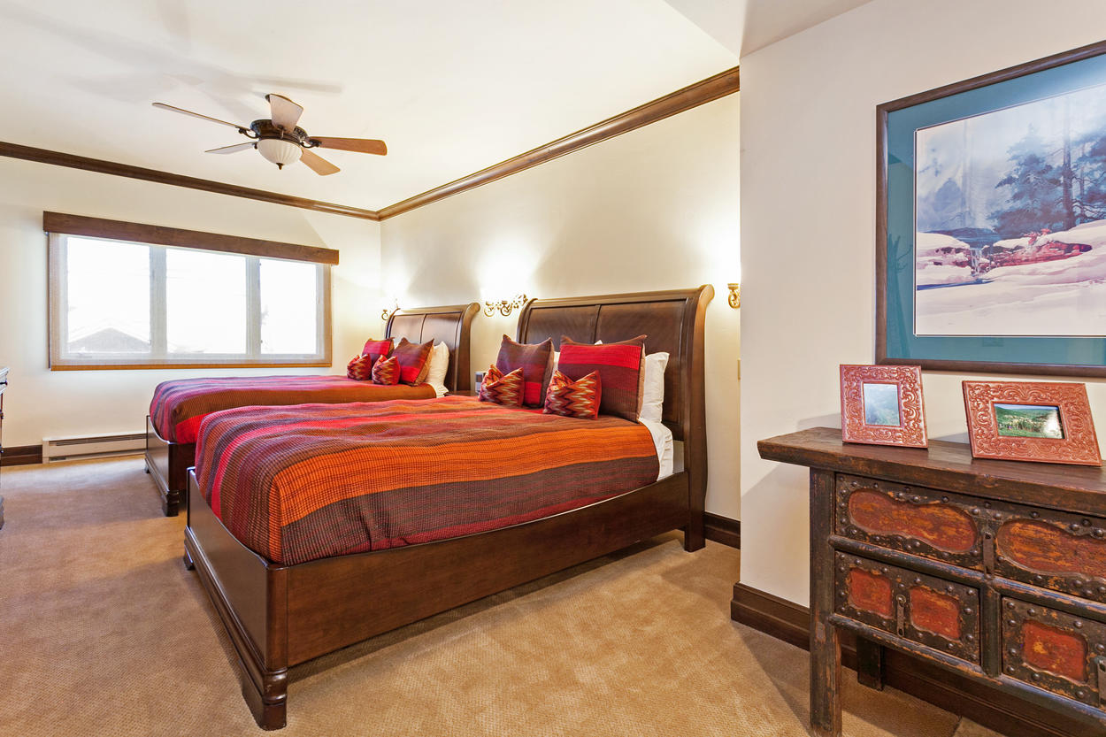 A third guest bedroom features two queen-size beds in a suite-style room.