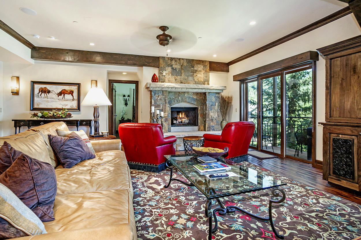 Two plush, tufted leather chairs are positioned around the huge stone fireplace in the living area.