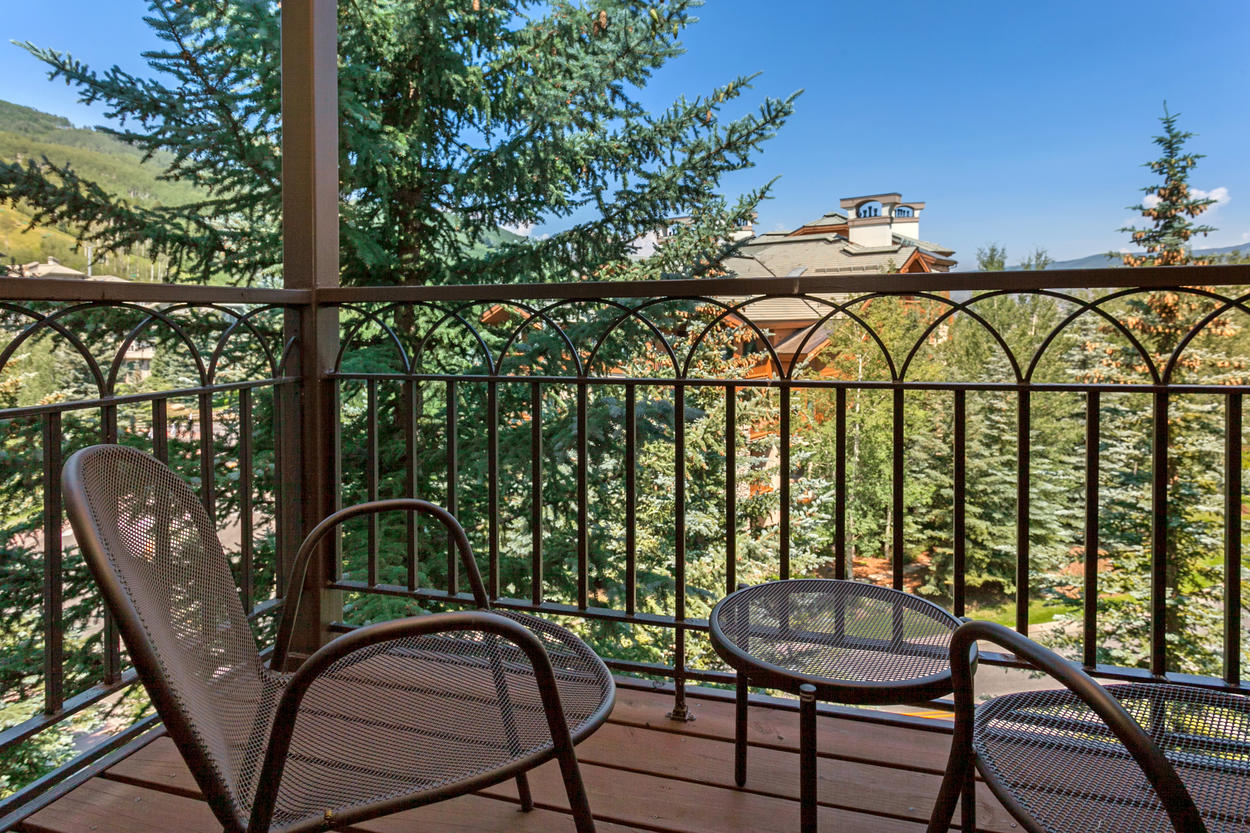 The spacious balcony has outdoor furniture for relaxing in the open mountain air.