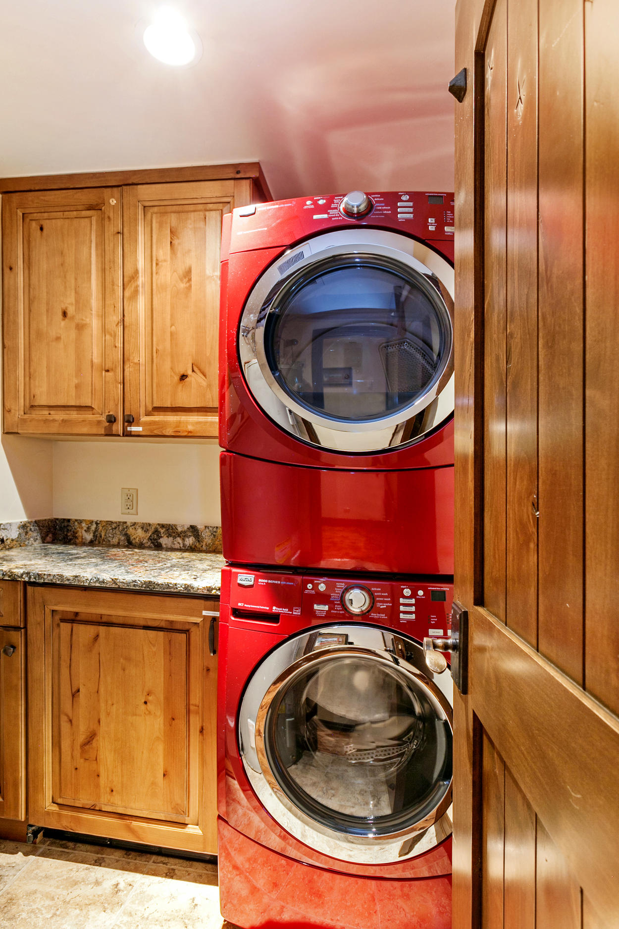 A tucked away laundry room features a stacked washer and dryer.
