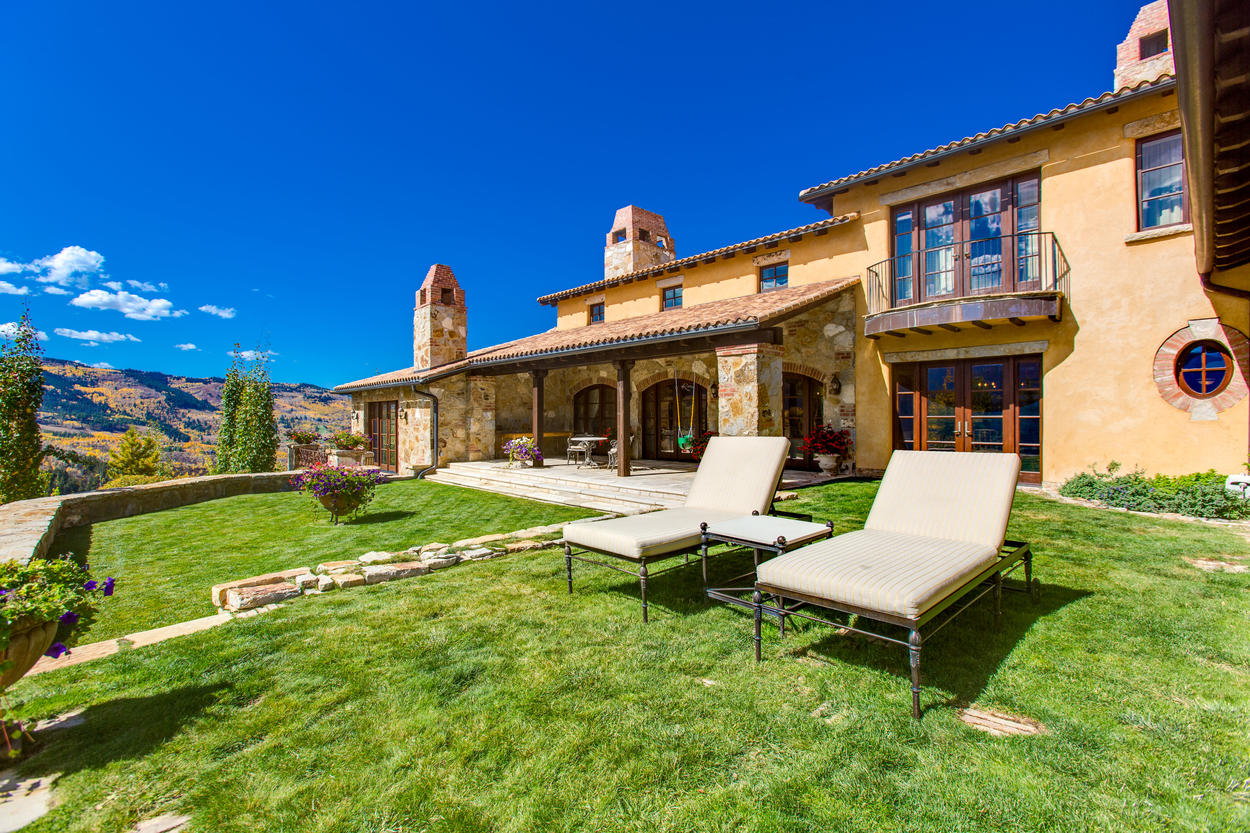 Lush greens surround the Tuscan-style home, and are perfect for lounging under the bright mountain sun.