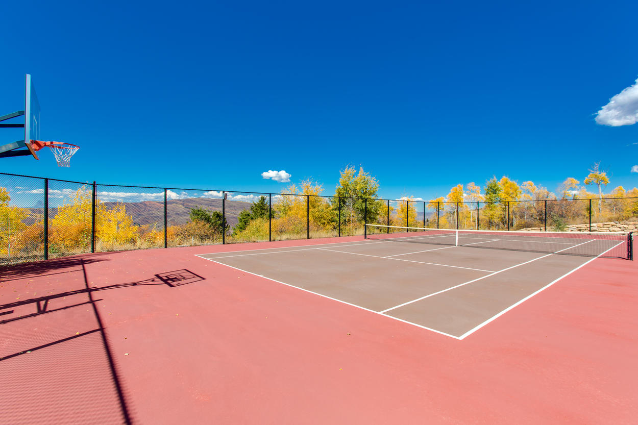 On the grounds of the home, there's a full-size tennis court, and a basketball hoop.