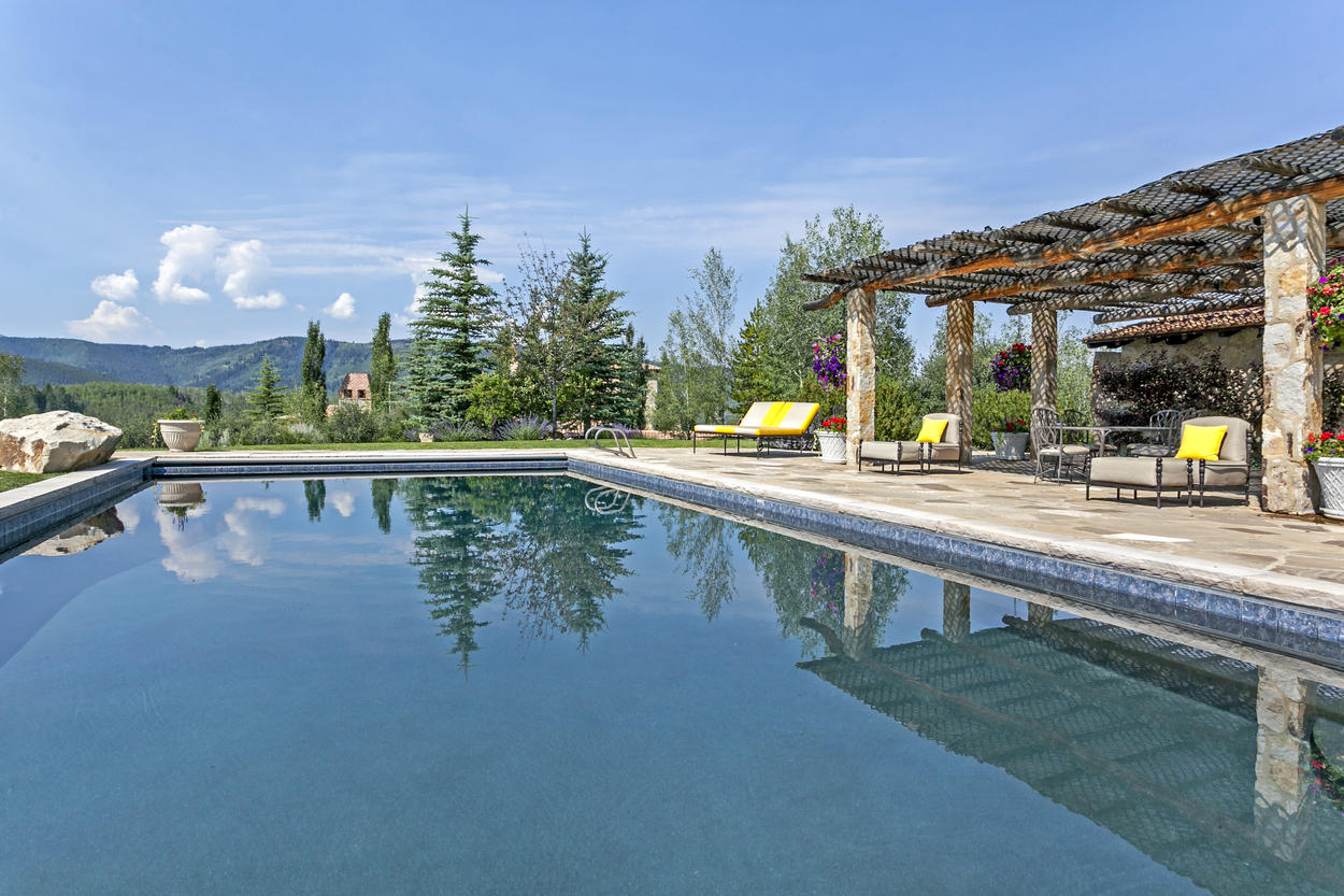 Relax by the pool under the shade of the expansive pergola.