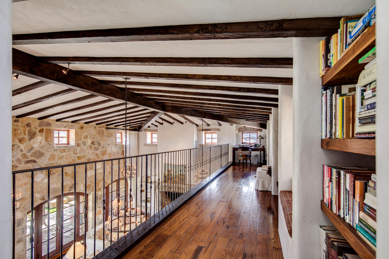 The upper level has a long hallway with bookcases and bench seating that overlooks the main living area below.