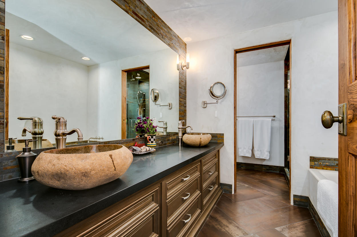 Each room has an attached ensuite bathroom with a shower, tub, and a large double vanity.