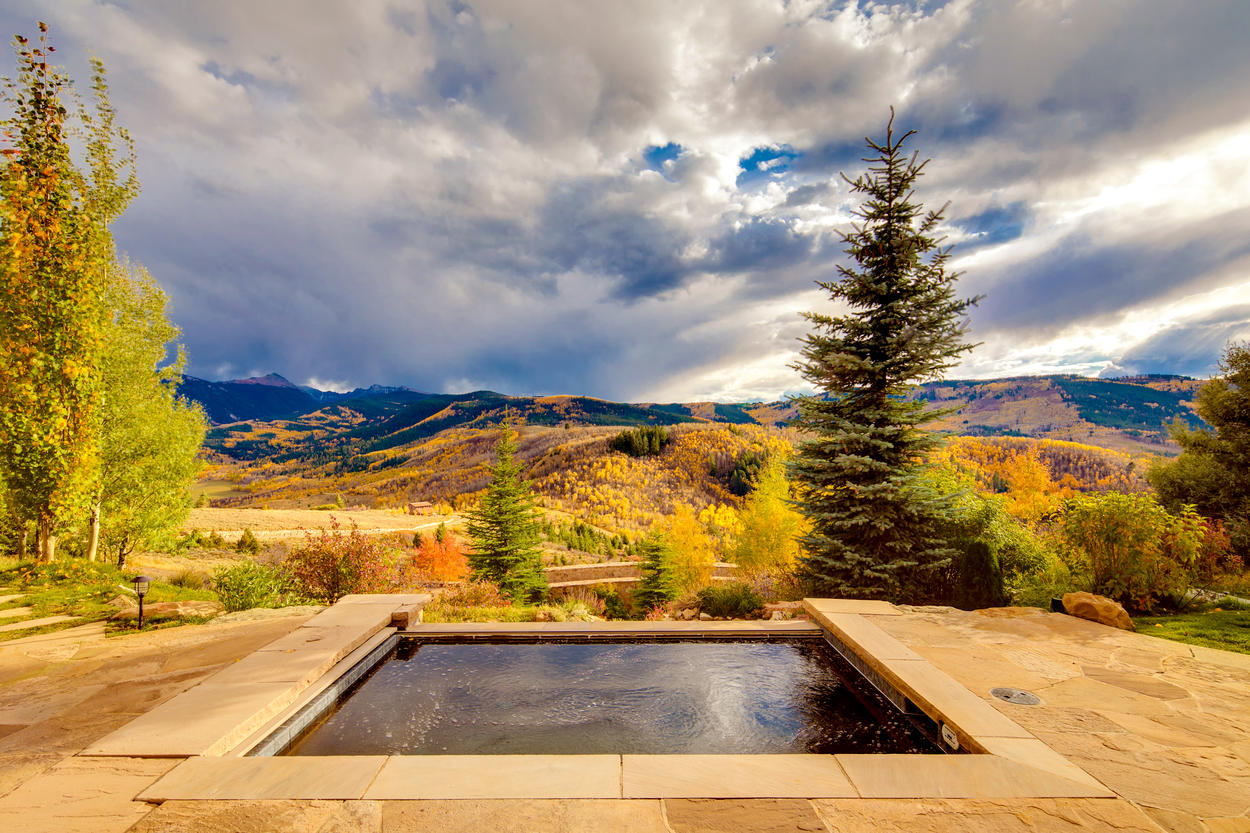 The infinity hot tub is at the edge of the property, overlooking the mountain ranges beyond.