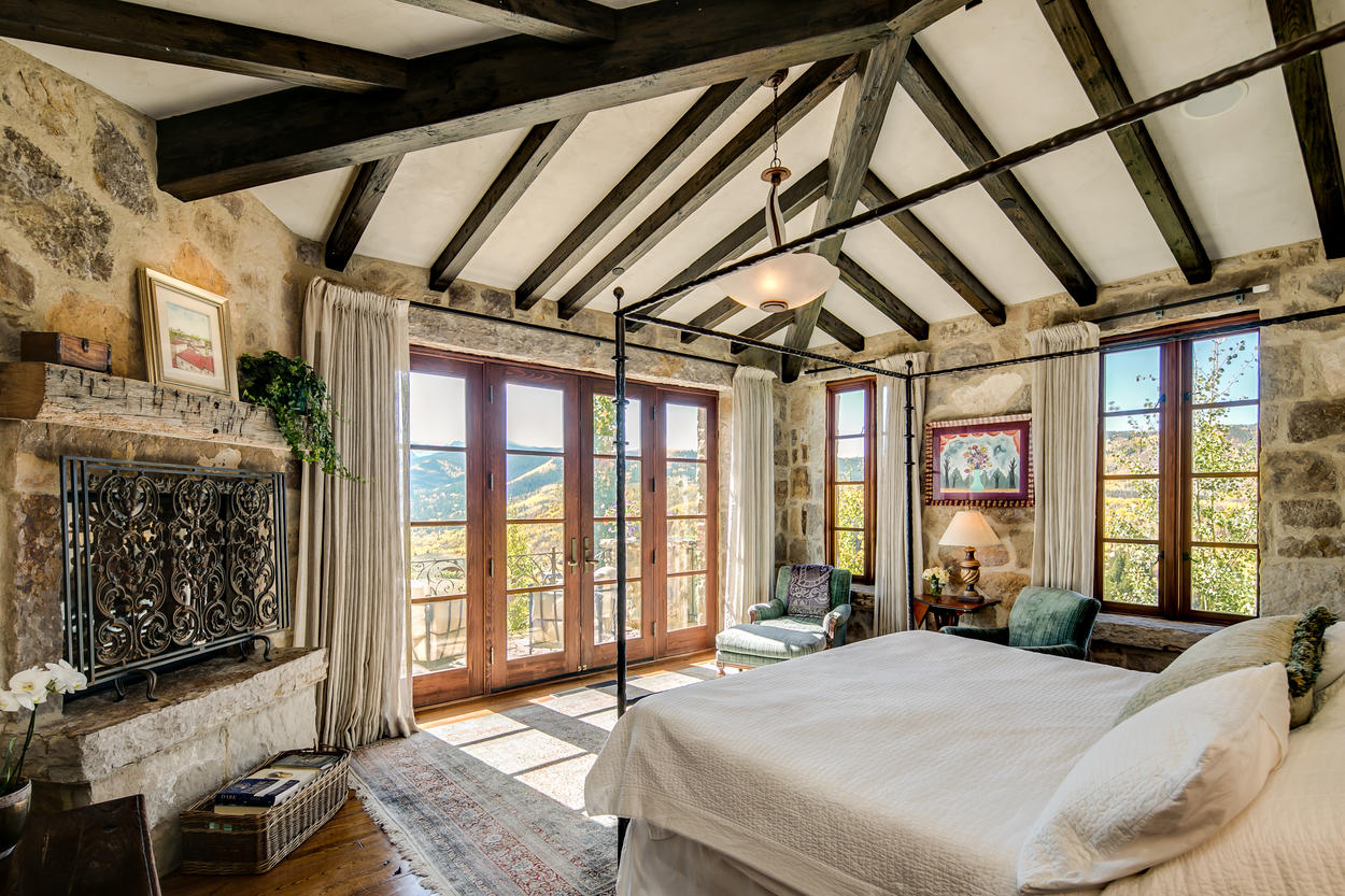 A grand fireplace sits in the corner of the Master Suite, and classic exposed wood beams run overhead.