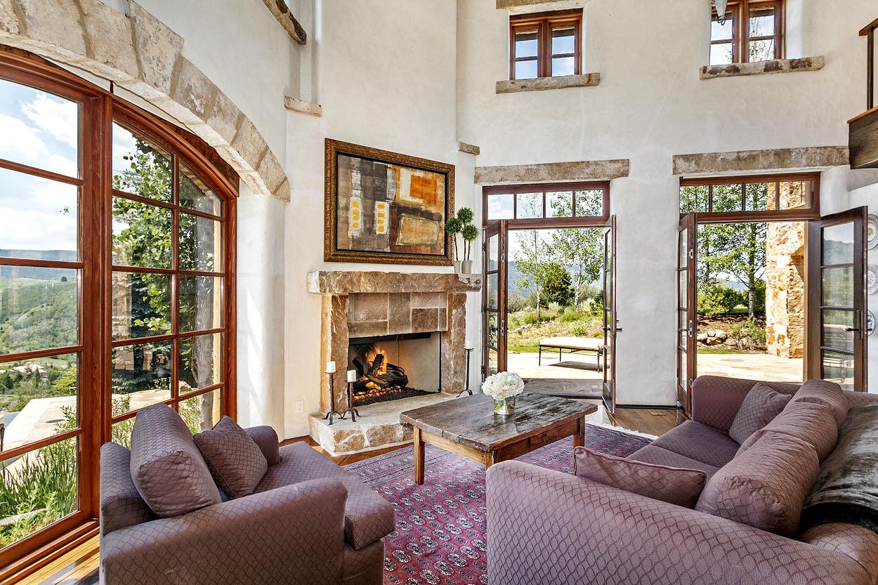 The guest house has its own living room, with French doors and a stone fireplace.