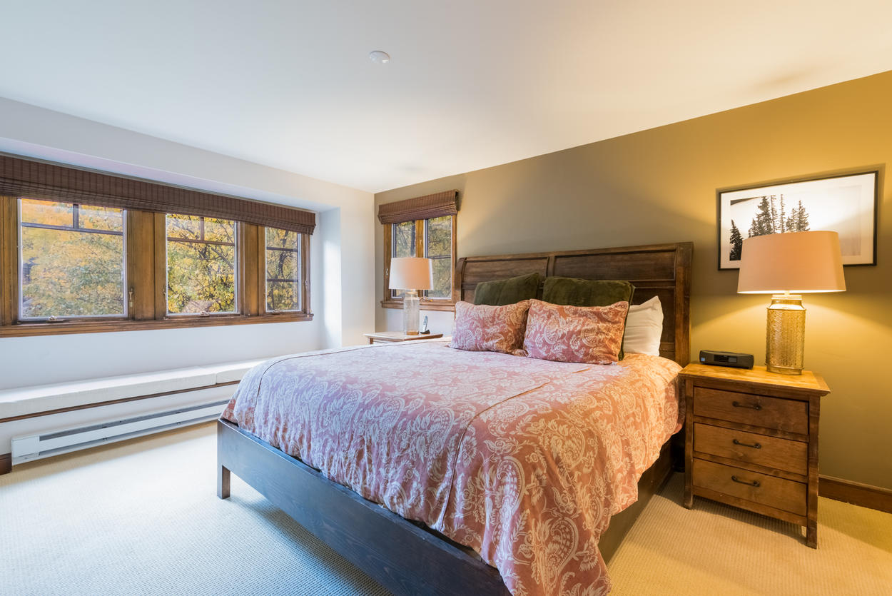 The master bedroom features a king bed and lots of warm wood finishes