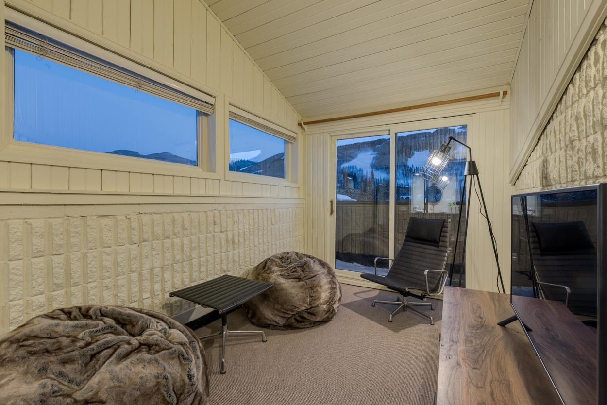 The private den off of the master suite offers plush seating, mountain views and access to another balcony