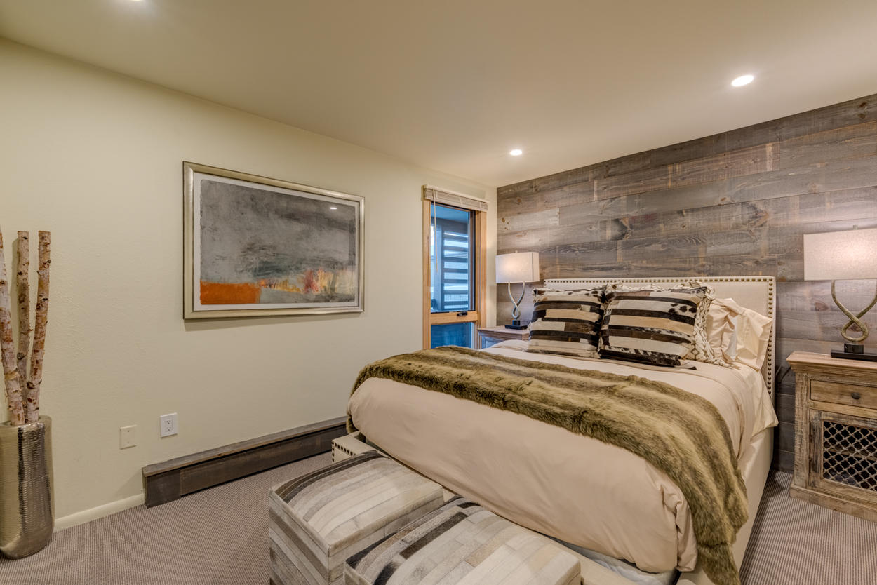 On the main level, Guest Bedroom 2 holds a queen bed and features a reclaimed wood accent wall
