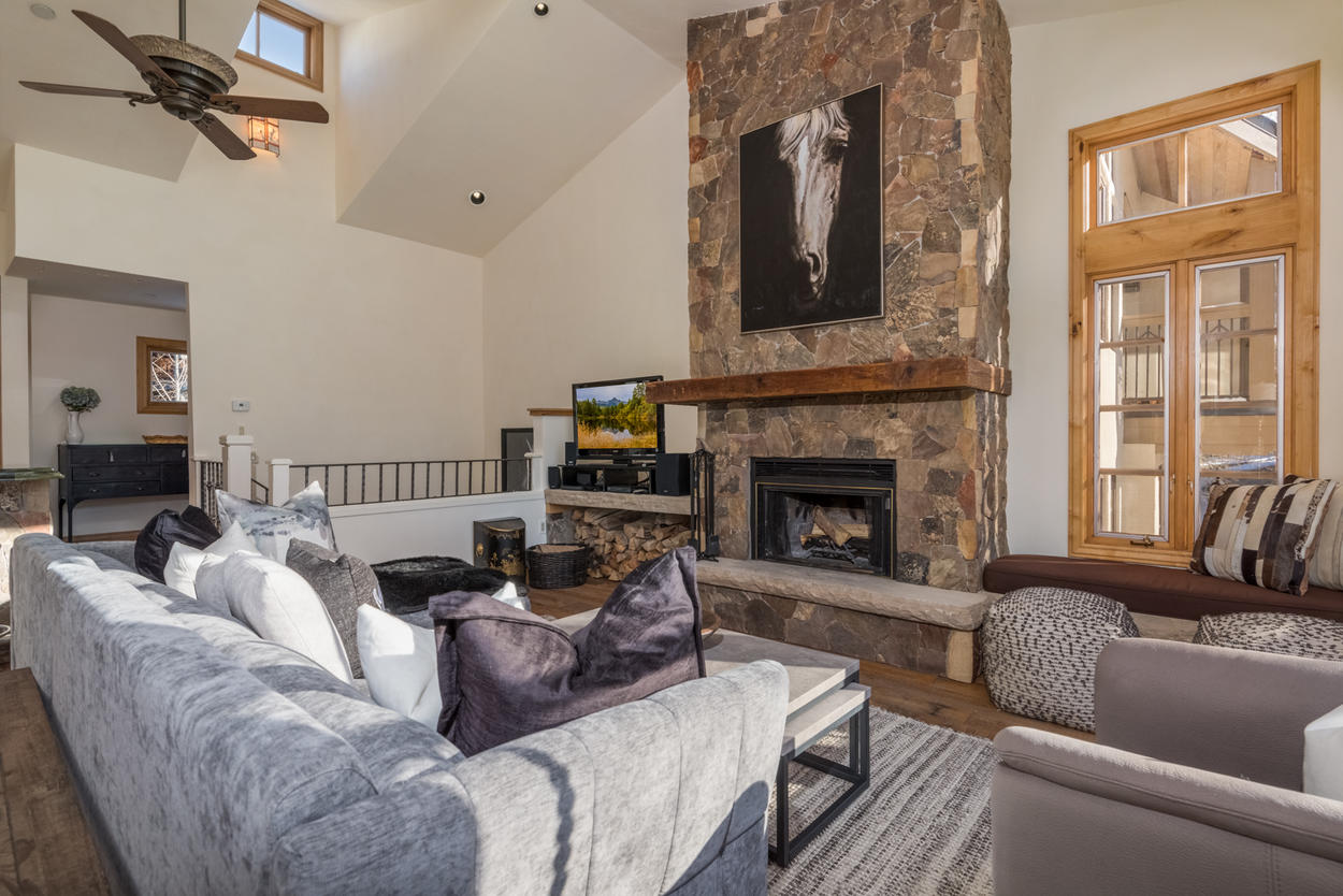 The living room features a flat screen tv, ceiling fan, and wood-burning fireplace