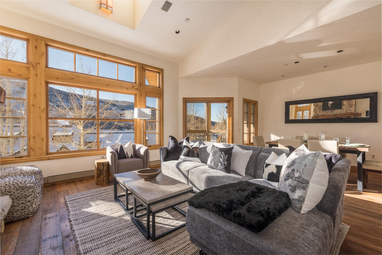 Enjoy the bright sunshine from the wall of windows in this large living space