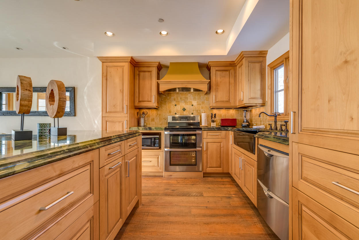 Stainless steel appliances and marble countertops enhance the custom cabinetry