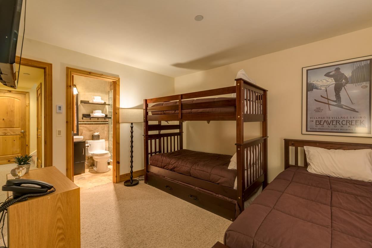 The lower level Bunk Bedroom features a total of 4 twin beds, between the bunk, extra twin, and hidden trundle