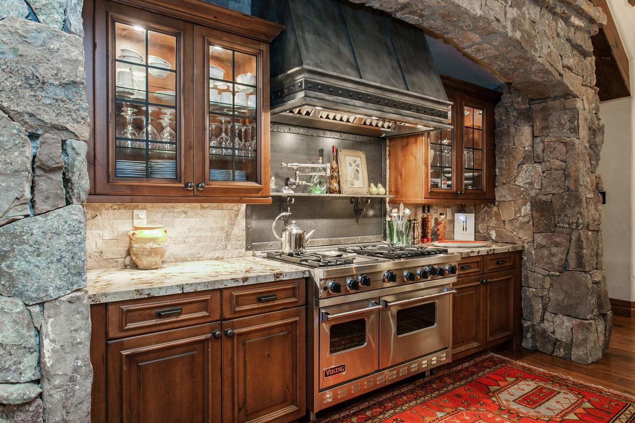 This kitchen features top-of-the-line appliances and finishes, including a pot-filler faucet over the dual Viking ranges