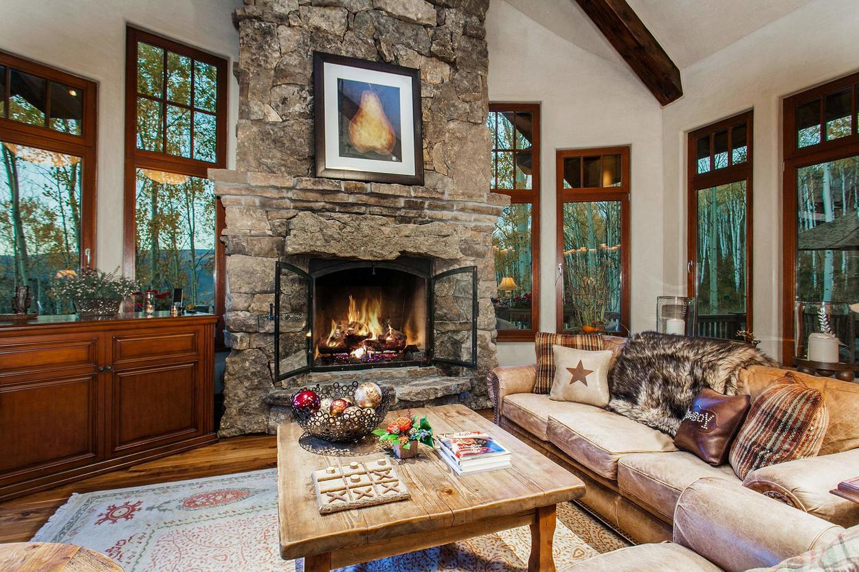 The Den on the main level features a flat screen tv (unpictured) and wood-burning fireplace
