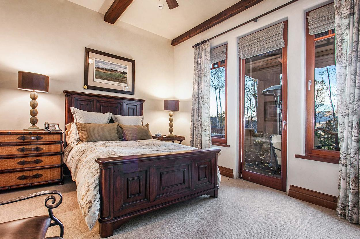 This lower level guest bedroom hosts a queen bed and ensuite, plus deck access