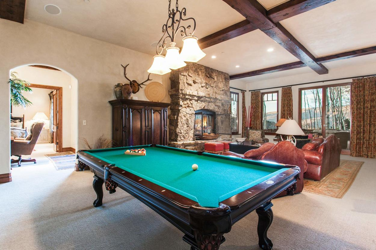 The Family Room on the lower level has a pool table and television tucked away in the cabinet