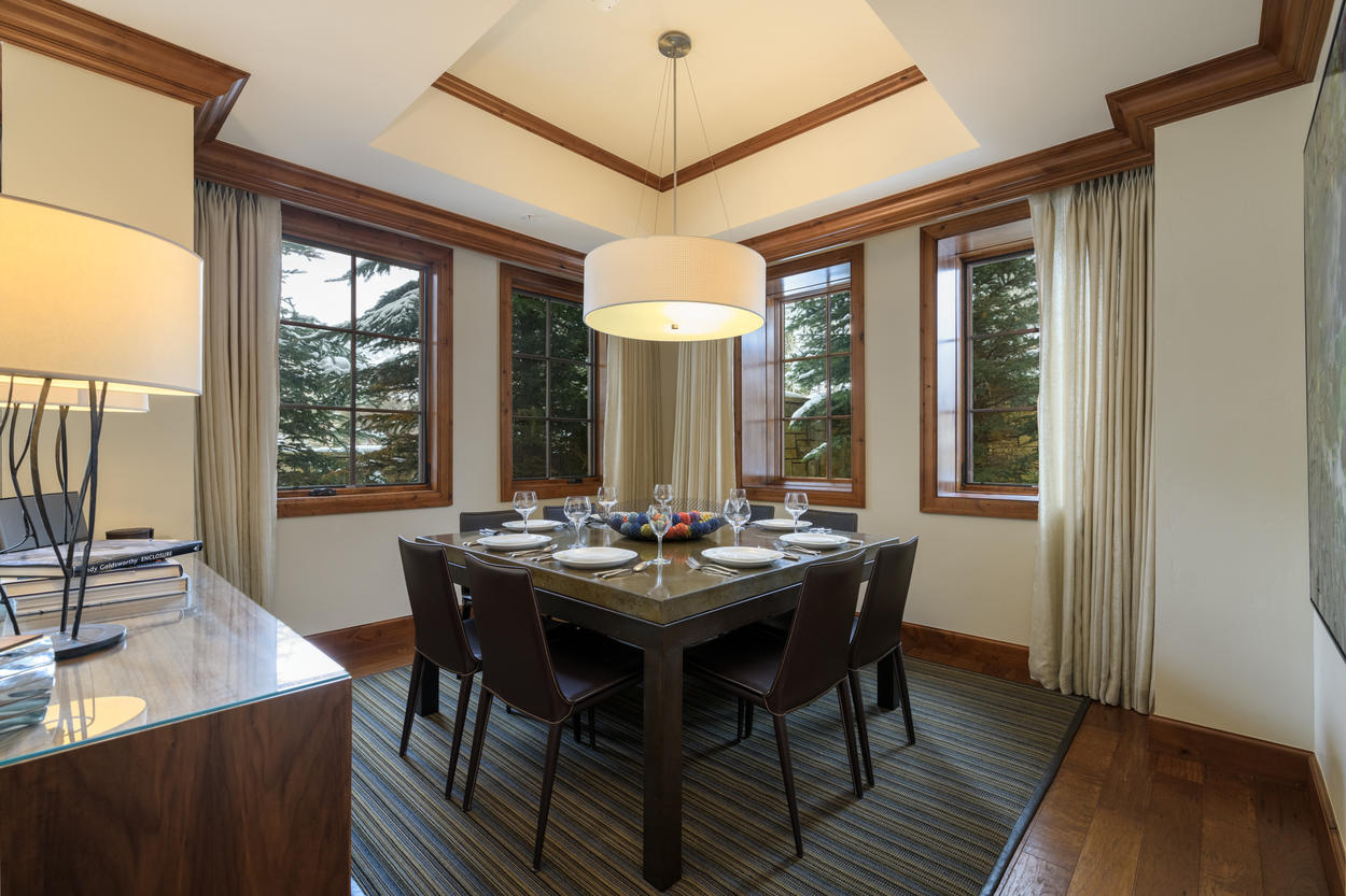 The dining area is tucked into the corner of the open concept room and is surrounded by windows.