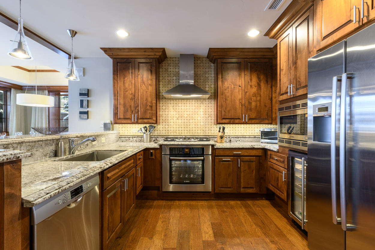 The full kitchen features a wine fridge and all-stainless steel appliances, including a 5-burner gas stove.