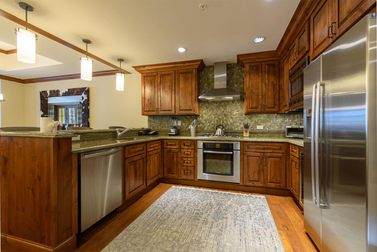 The kitchen features granite countertops and all stainless steel appliances.