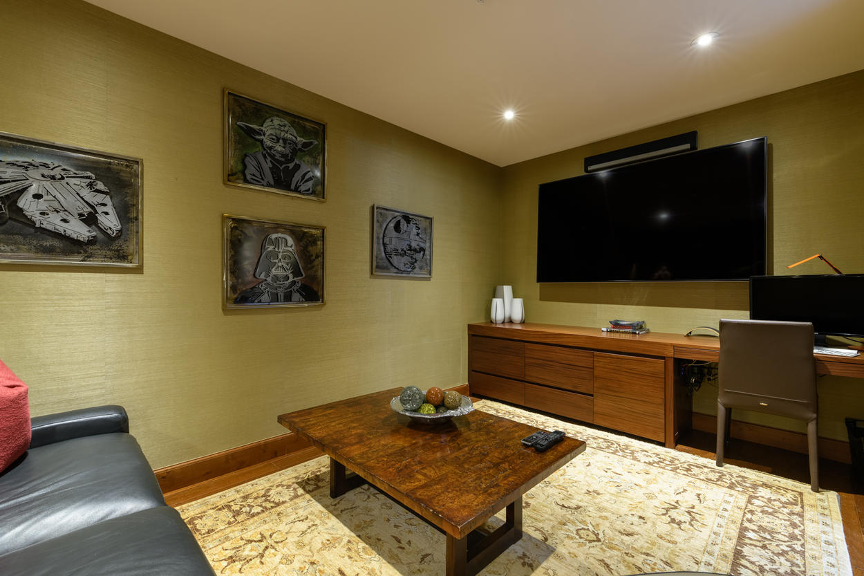 As a theater, this room features a large flat screen TV. A desk in the corner easily turns this space into a workstation.