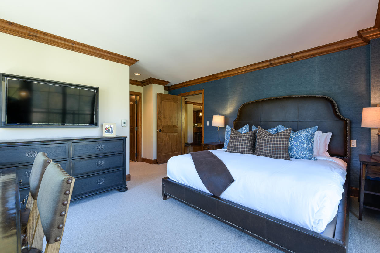 The Master Bedroom has a king-size bed and a mounted flatscreen TV.