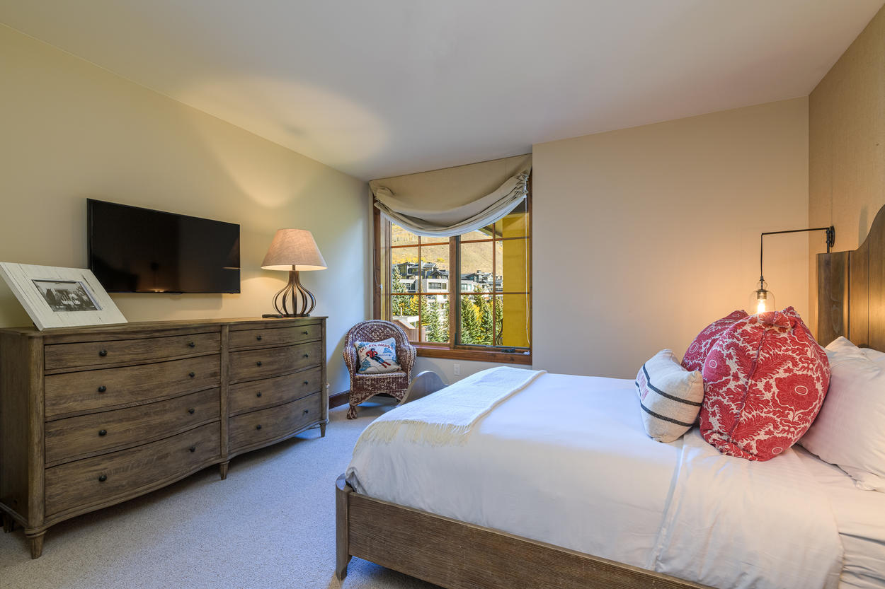 The second guest bedroom has a queen-size bed and a mounted TV.