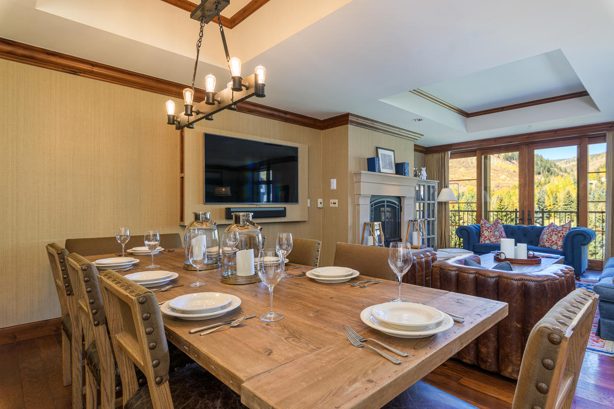 The large farm table in the dining area can seat up to 8 guests.