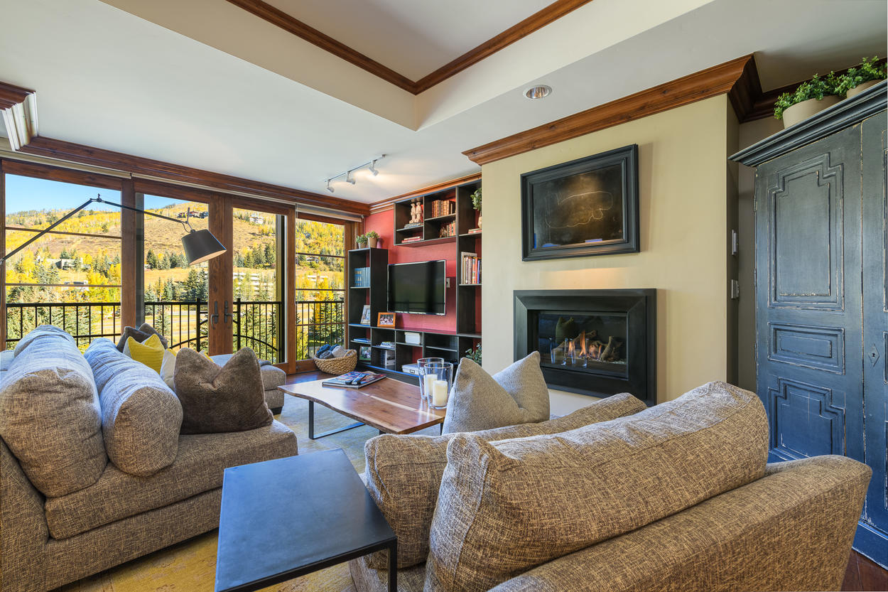 The large living area features a wall-mounted TV, gas fireplace, and floor-to-ceiling windows.
