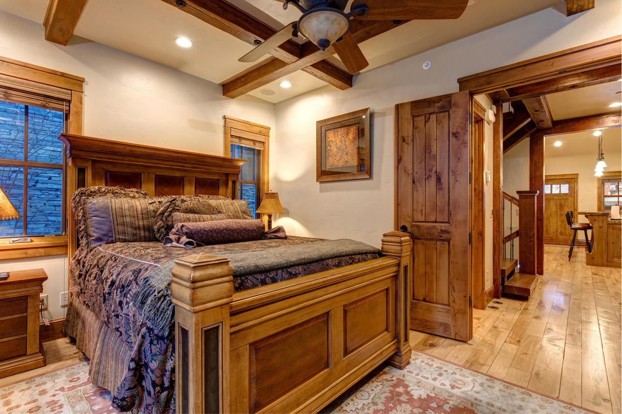 On the second floor, the Queen Guest Bedroom has elegant crossbeam work, as well as its own TV and fireplace.