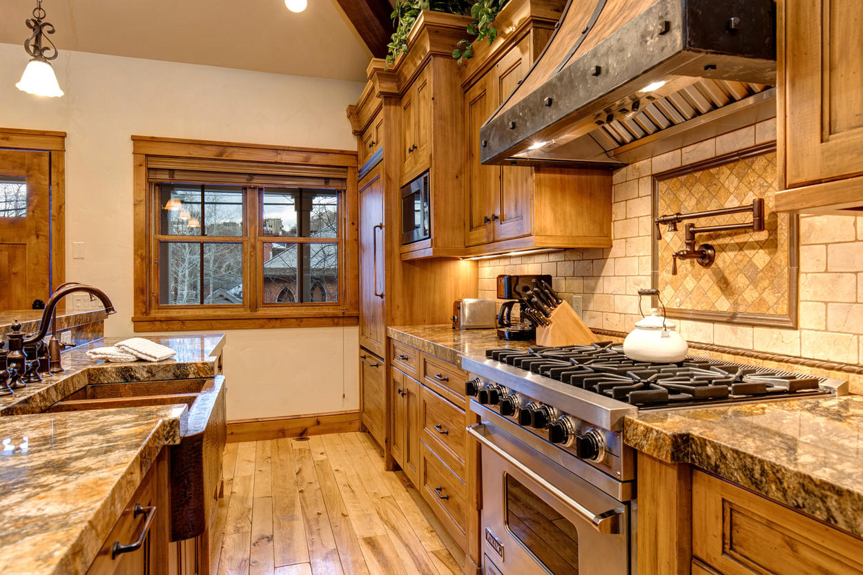 The exquisitely designed galley kitchen is segmented by a long granite breakfast bar.