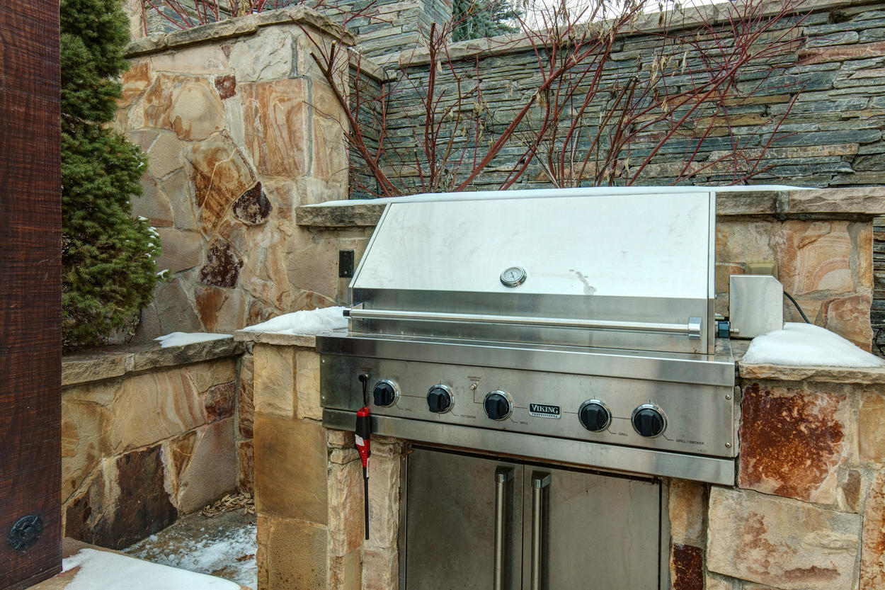 A gas grill is built within a large stone frame on the back patio.