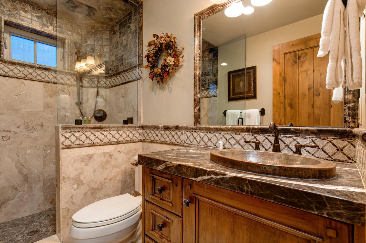 The elegant, dark vanity countertop pairs with the ceiling tilework in the stand-alone shower.