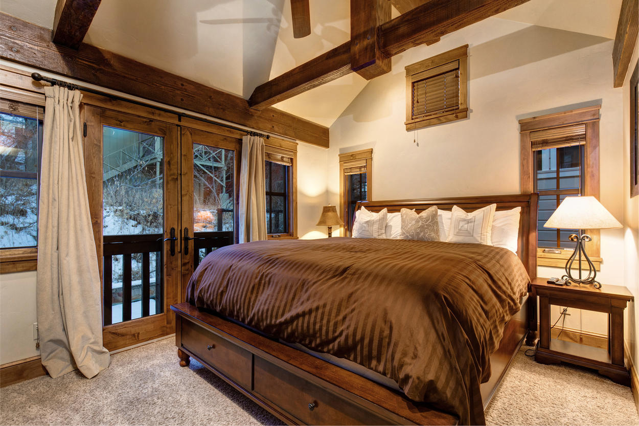 The Master Bedroom is a sumptuous retreat with exposed wood beams and lofted ceilings.