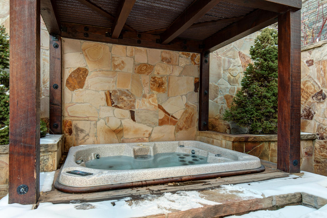 A hot tub is tucked under a grand wooden cover.