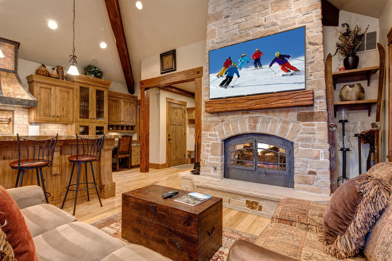 The main living area has a huge stone fireplace and TV set above the wood mantle.