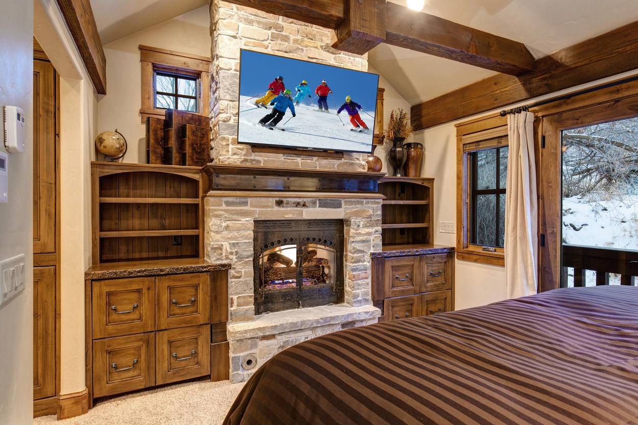 A mounted TV sits above the fireplace in the Master Bedroom.