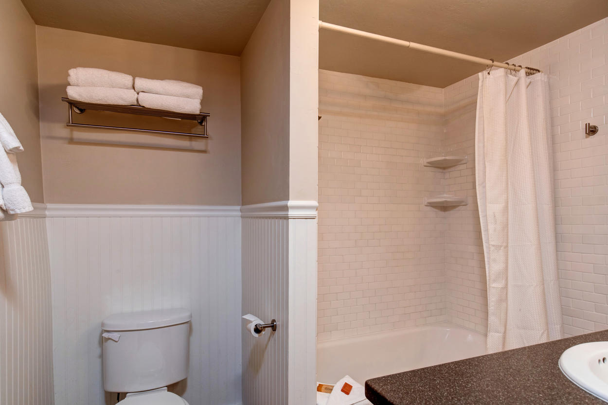 The first-floor guest bathroom has a combination tub/shower and is decorated in classic white tile.